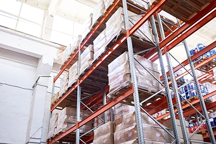 Low angle view at tall storage shelves with packed goods in warehouse, background with copy space
